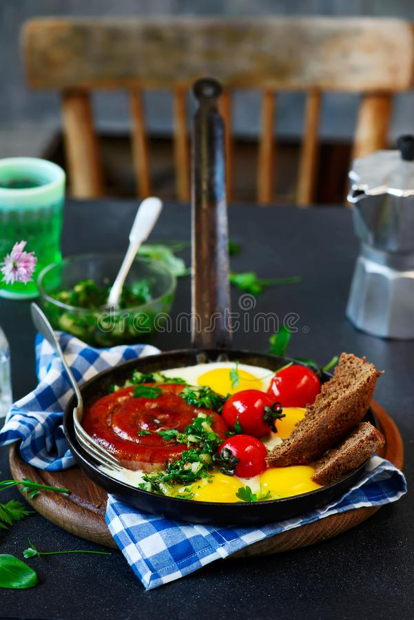 Fried eggs with sausages and green salsa stock photos