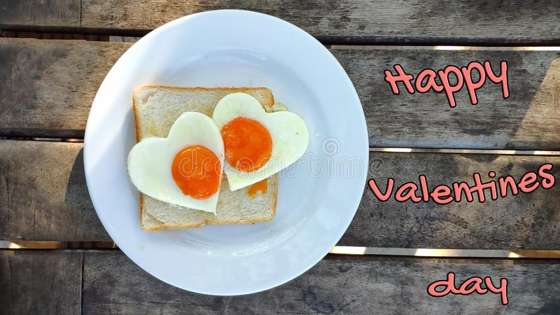 Fried eggs in the shape of a heart at toast on white plate and wooden table. Breakfast with love. Inscription Happy Valentine`s royalty free stock images