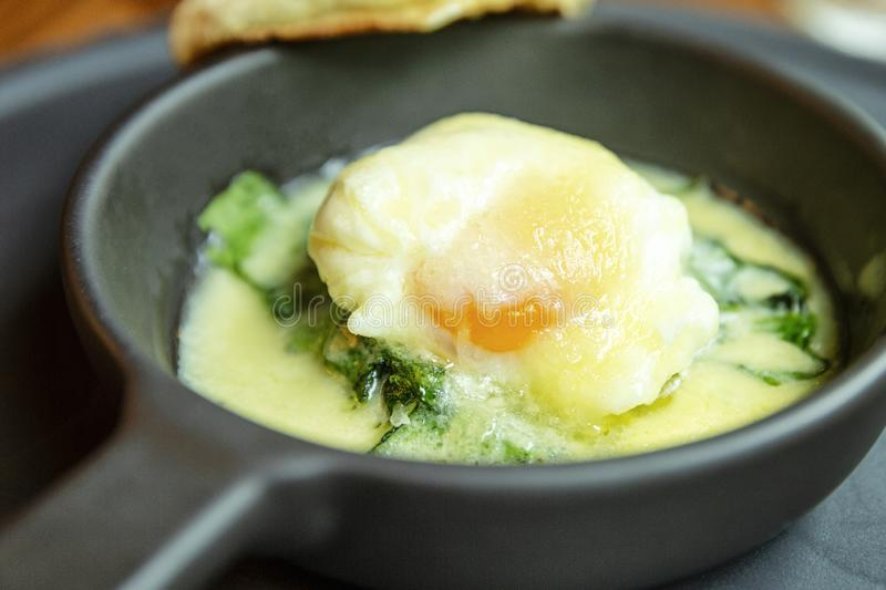 Fried eggs in a small cast-iron portion pan on the table. Healthy beautifully decorated breakfast in the cafe. Close-up stock photo