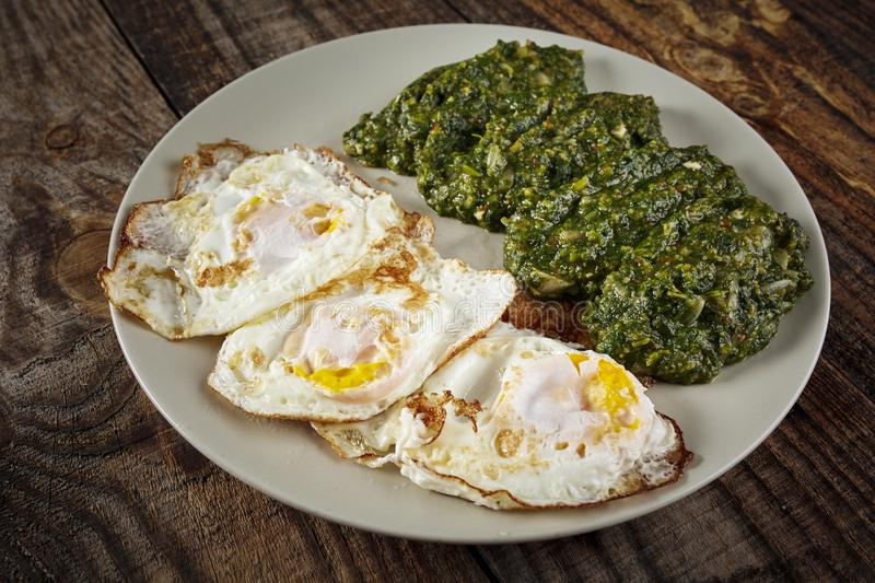 Fried eggs with spinach. Closeup of fried eggs with spinach side dish stock photos