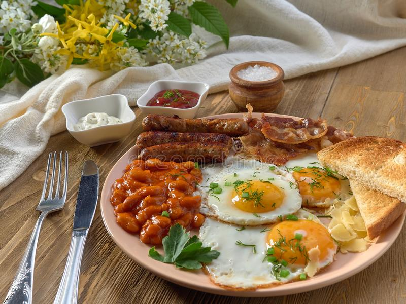 Fried eggs,stewed beans,delicious sausages and toast. stock photo