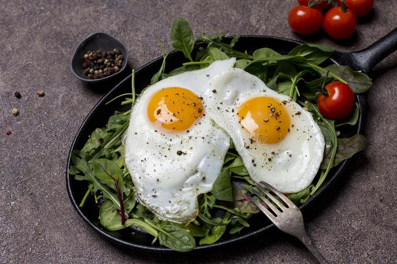 Fried eggs sunny side up on pan with herbs, cherry tomatoes and pepper, with fork an brown background. Concept of healthy stock photos