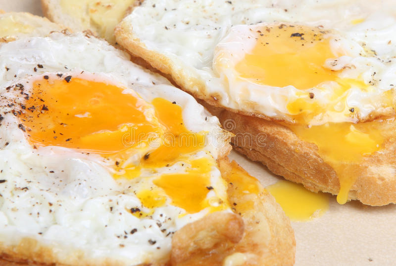 Fried Eggs on Toast. Two fried eggs on rustic-style thick toast royalty free stock photos