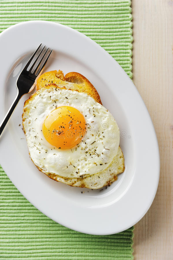 Fried eggs with toast. Fried eggs in oval white plate with toast on the green tissue stock photography