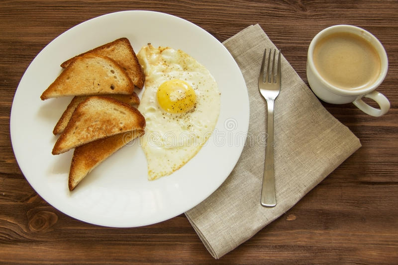 Fried eggs with toast and coffee. On wooden royalty free stock photo