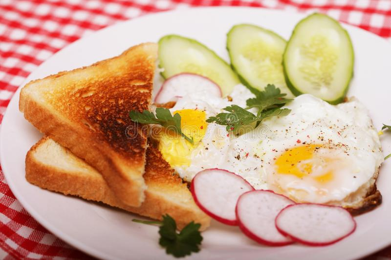 Fried eggs and toast - excellent breakfast. On white plate stock photography