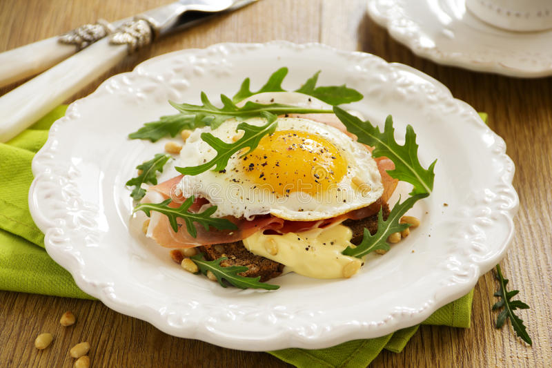 Fried eggs on toast. With prosciutto stock photography
