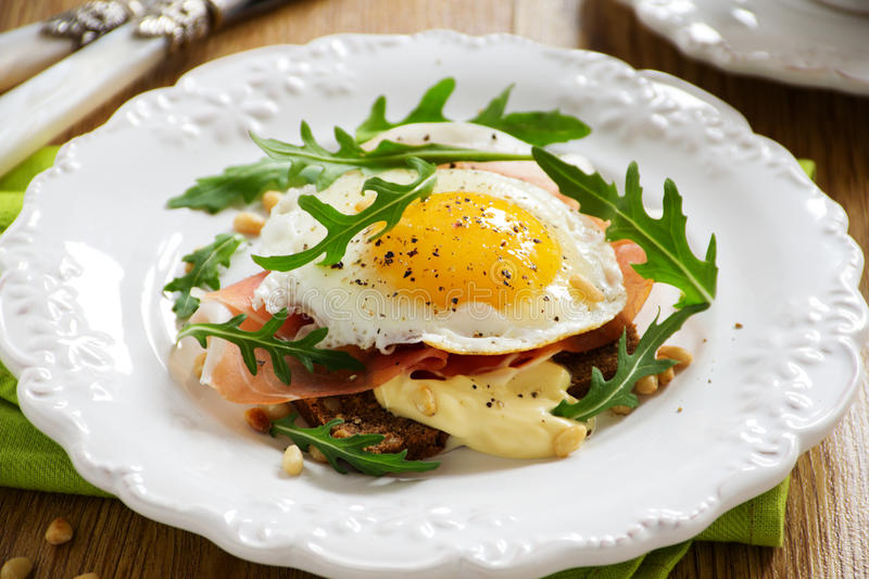 Fried eggs on toast. With prosciutto stock images