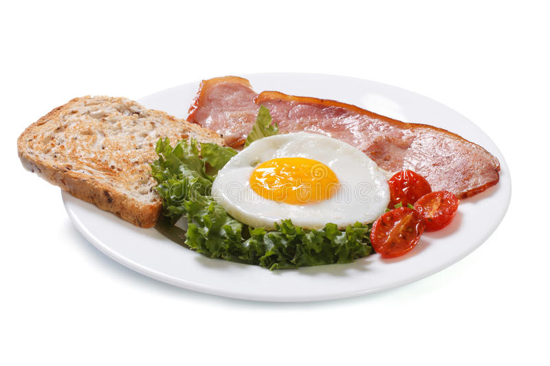 Fried eggs with tomato, ham and bread. Isolated stock image
