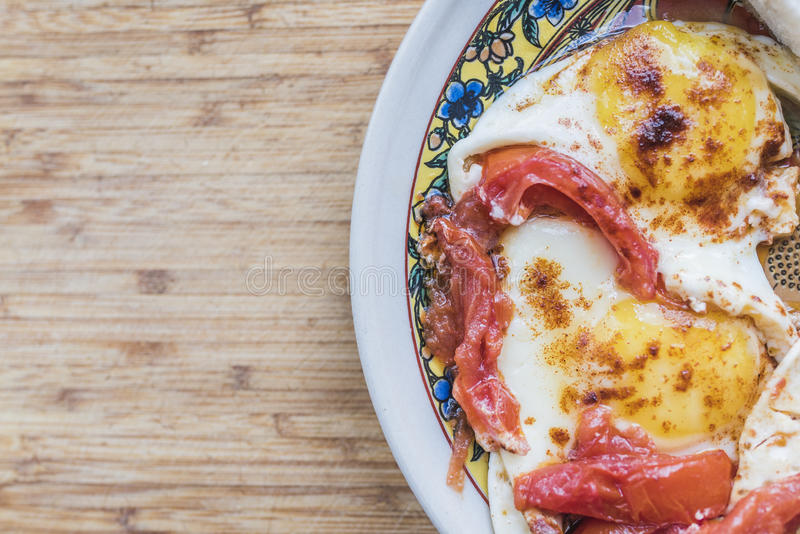 Fried eggs with tomatoes on color plate royalty free stock image