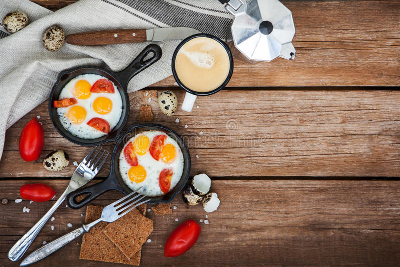 Fried eggs with tomatoes in frying pans stock images
