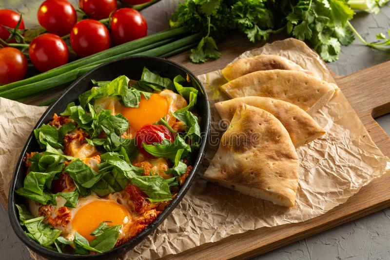 Fried eggs with tomatoes and herbs in an oval black dish stock photography