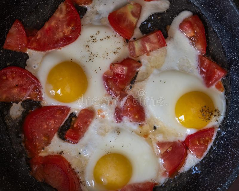 Fried eggs with tomatoes in a pan, close-up royalty free stock photo