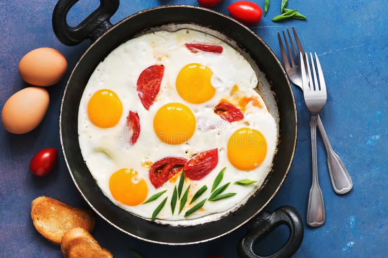 Fried eggs with tomatoes served in a pan with toast on a blue background. Flat lay, tinted photo. Fried eggs with tomatoes served in a pan with toast on a blue stock images