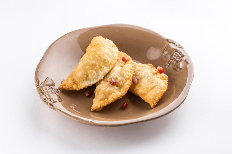 Fried empanadas with pomegranate on brown plate isolated on white background royalty free stock photography