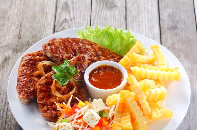 Fried Escalope met Gebraden gerechten op Witte Plaat royalty-vrije stock afbeeldingen