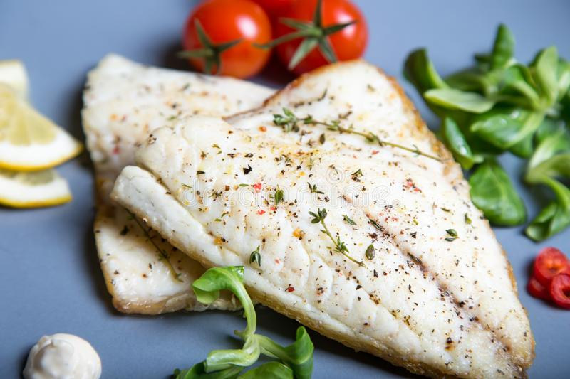 Fried fillet dorado fish with tomatoes, lemon and corn salad. Selective focus, close-up stock images