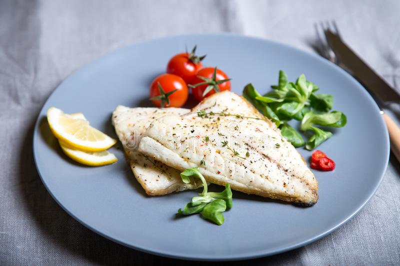 Fried fillet dorado fish with tomatoes, lemon and corn salad. Selective focus, close-up royalty free stock image