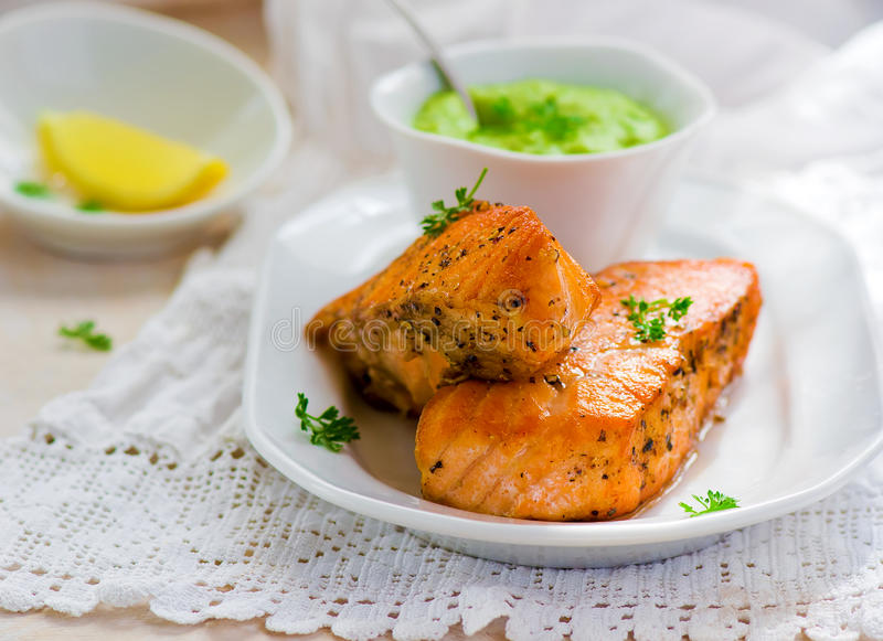 Fried fillet of a salmon with green peas sauce stock photography
