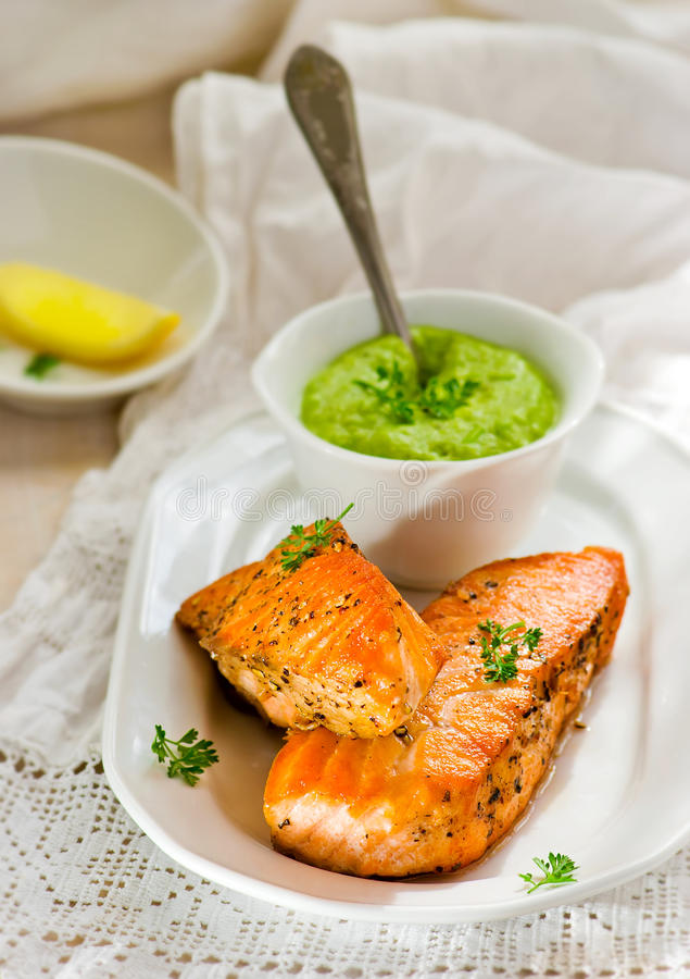 Fried fillet of a salmon with green peas sauce royalty free stock photography