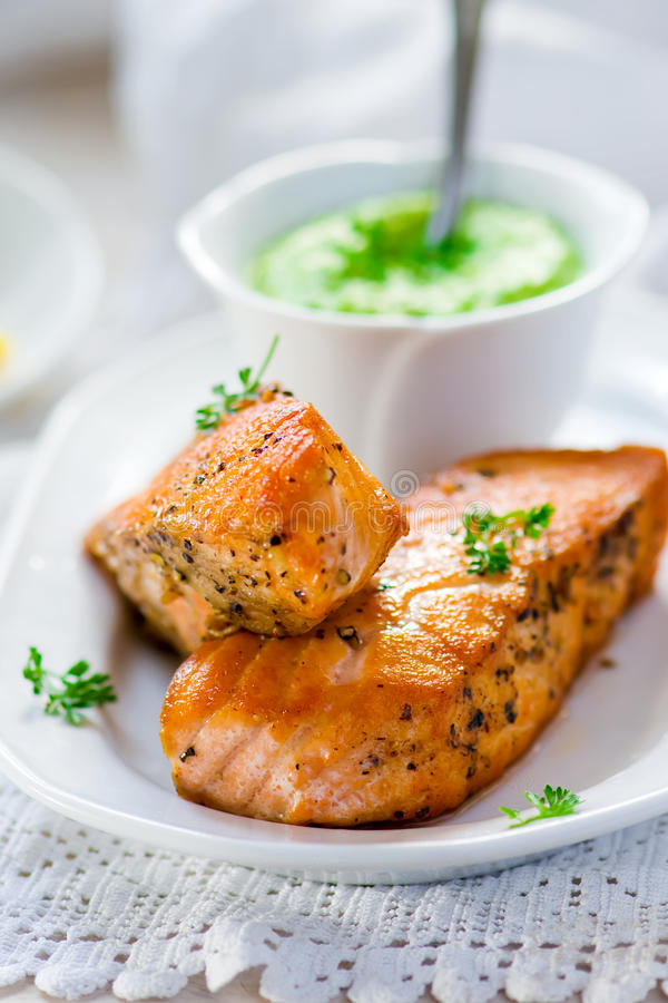 Fried fillet of a salmon with green peas sauce stock photos