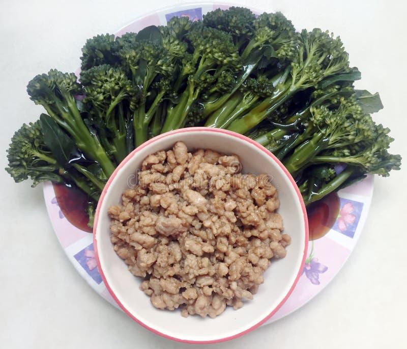 Fried finhackade griskött som tjänades som med broccoligrönsaker som fylldes med oy arkivfoton