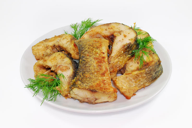 Fried fish, Alaska Pollock or Hake slices on a plate isolated Against white background royalty free stock photo