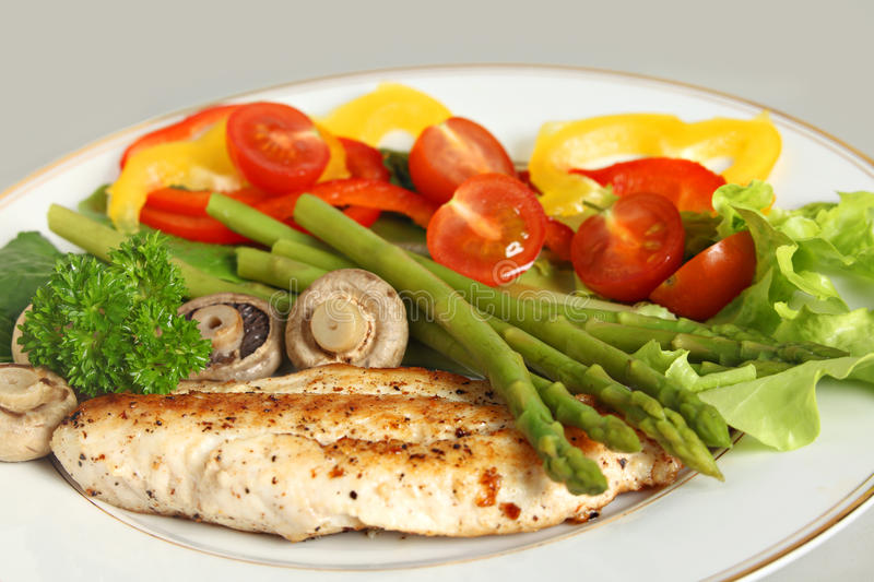 Fried fish, asparagus and salad royalty free stock images