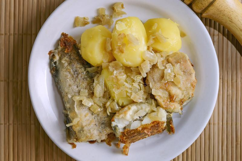 Fried fish and boiled potatoes lies on a plate on a bamboo napkin. Close-up, selective focus. Close-up stock image