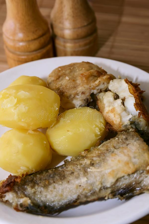 Fried fish and boiled potatoes on a plate. Close-up stock image