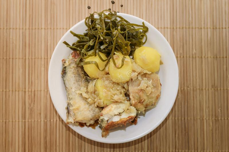 Fried fish and boiled potatoes on a plate. Close-up royalty free stock photo