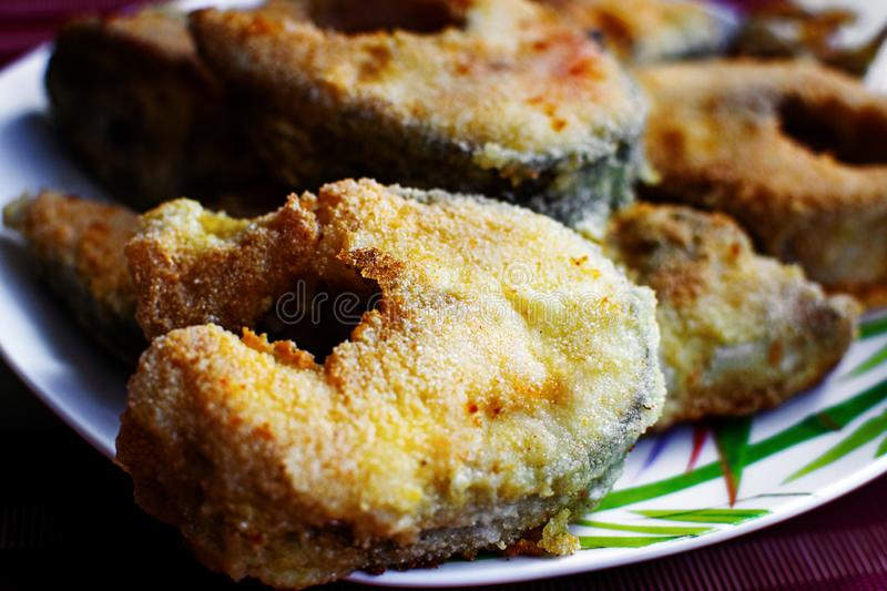 Fried fish in breading on a plate. Tasty and healthy fried fish in breading on a plate royalty free stock photo