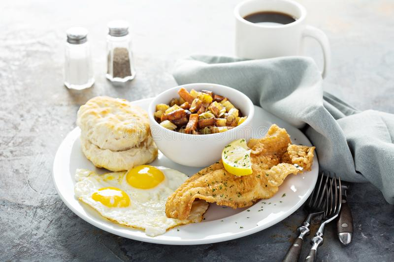 Fried fish breakfast with sunny side up eggs stock photography