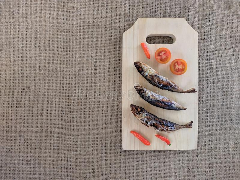 Fried fish bump on wooden cutting board, served with chilies and tomatoes royalty free stock photography