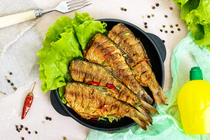 Fried fish carp sazan on a cast-iron frying pan with lettuce leaves on a light background. royalty free stock image