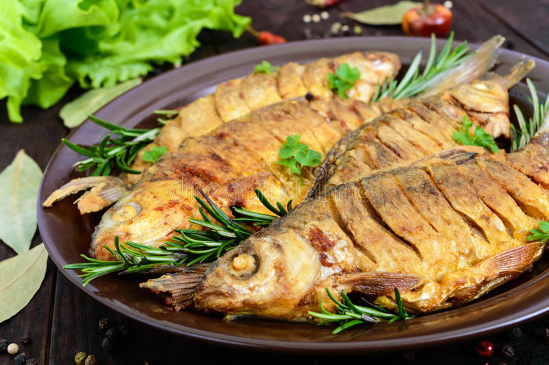 Fried fish carp sazan on a ceramic bowl with branches of rosemary stock photo