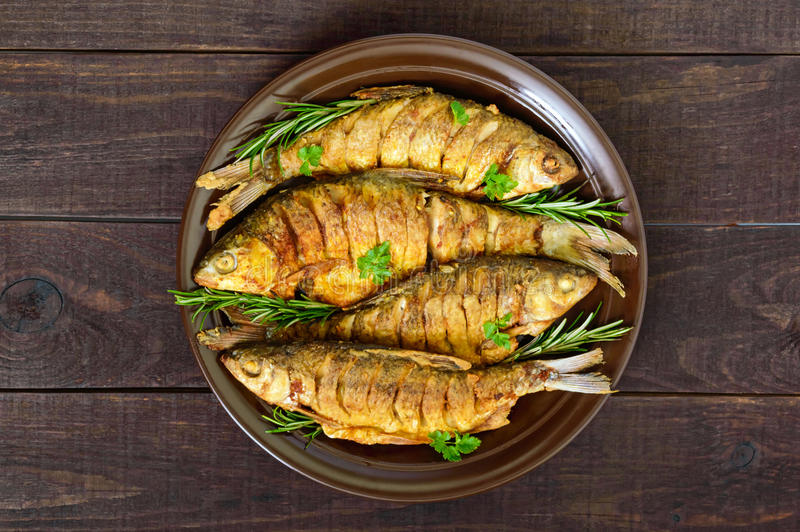 Fried fish carp sazan on a ceramic bowl with branches of rosemary stock photos