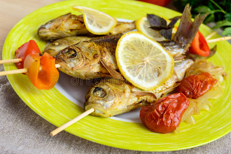 Fried fish (carp) on skewers with pieces bell pepper, sun-dried tomatoes and lemon. royalty free stock image