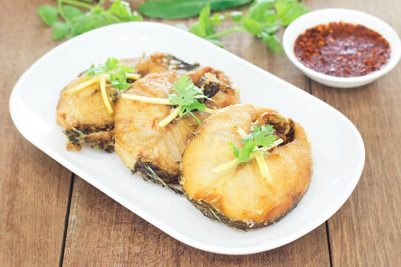 Fried fish with chili sauce on a white plate. stock image