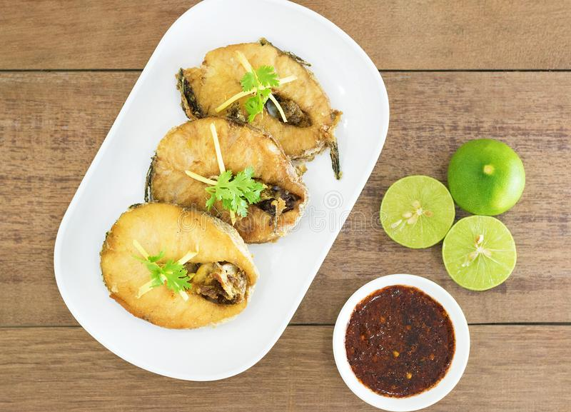Fried fish with chili sauce on a white plate. stock images