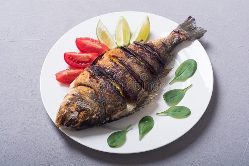 Fried fish dorado with lime , tomatoes and spinach. Sea food background stock photography