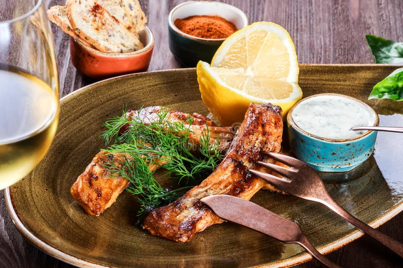 Fried fish fillet with cheese sauce, greens and lemon on plate on wooden background. Hot fish dish. Fried fish fillet with cheese sauce, greens and lemon on stock photo
