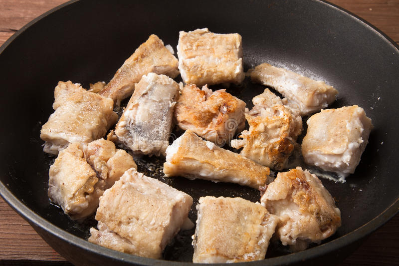 Fried fish fillet on a frying pan stock photography