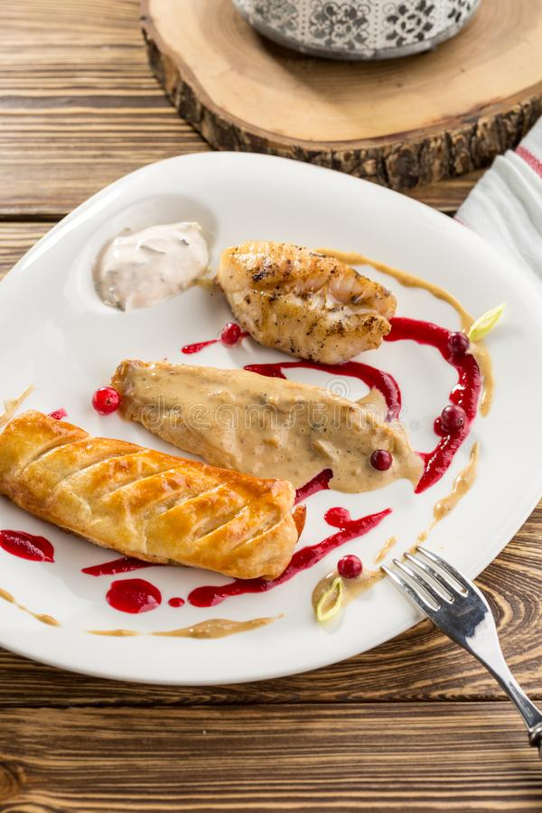 Fried fish fillet and pie with mushroom sauce on wooden table stock images