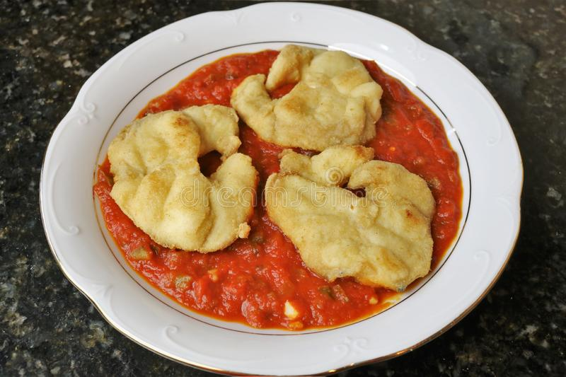 Fried fish fillets with tomato sauce stock images