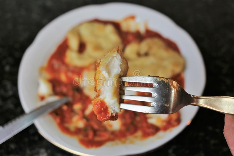 Fried fish fillets with tomato sauce. This is a recipe for Mediterranean cuisine. The sliced fish is on the tomato inside a white plate with a black background stock photos