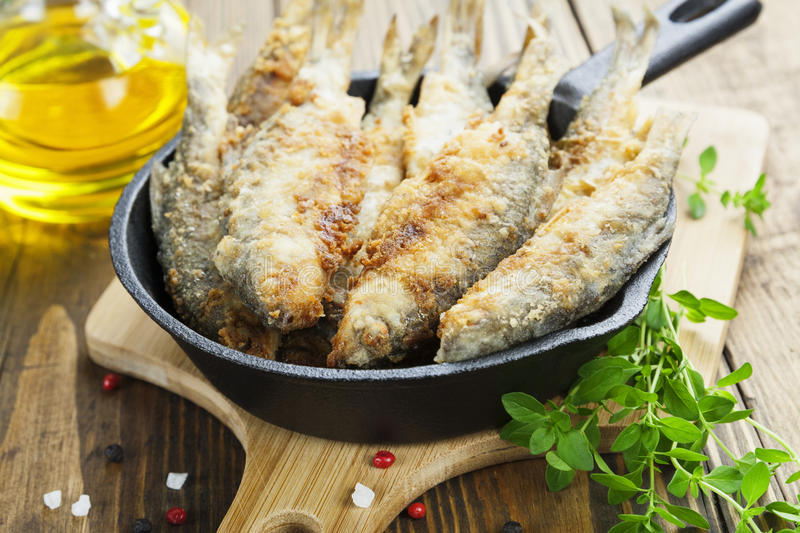 Fried fish in a frying pan. On the table stock images