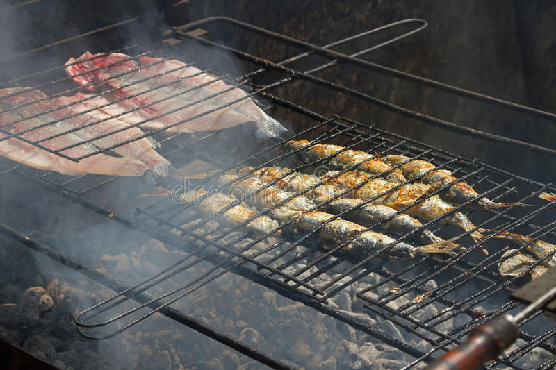 Fried fish on a hot coal. stock photography