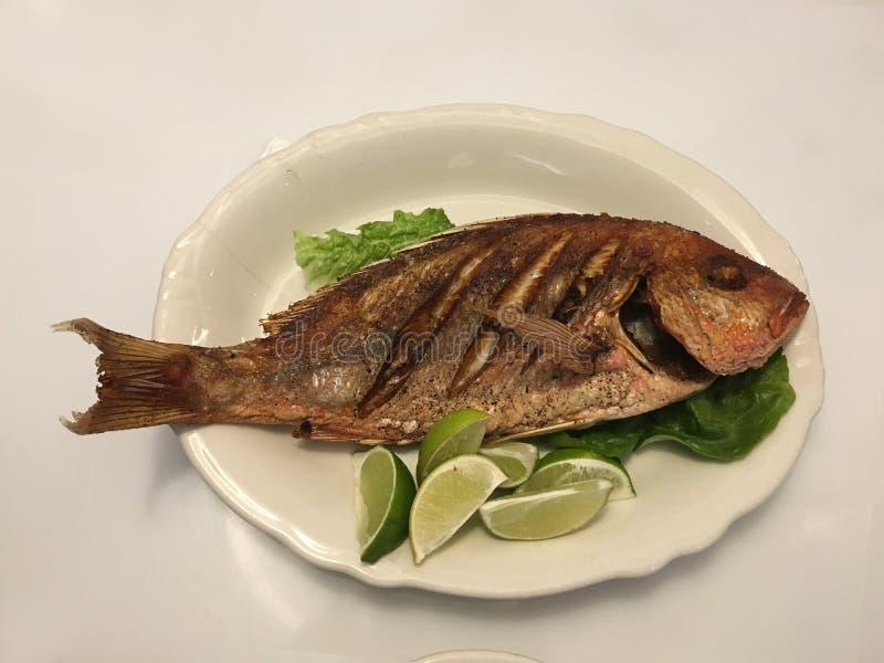 Fried Fish mit Kopf auf Kopfsalat-Zitronen-weißer ovaler Platte lizenzfreie stockfotografie