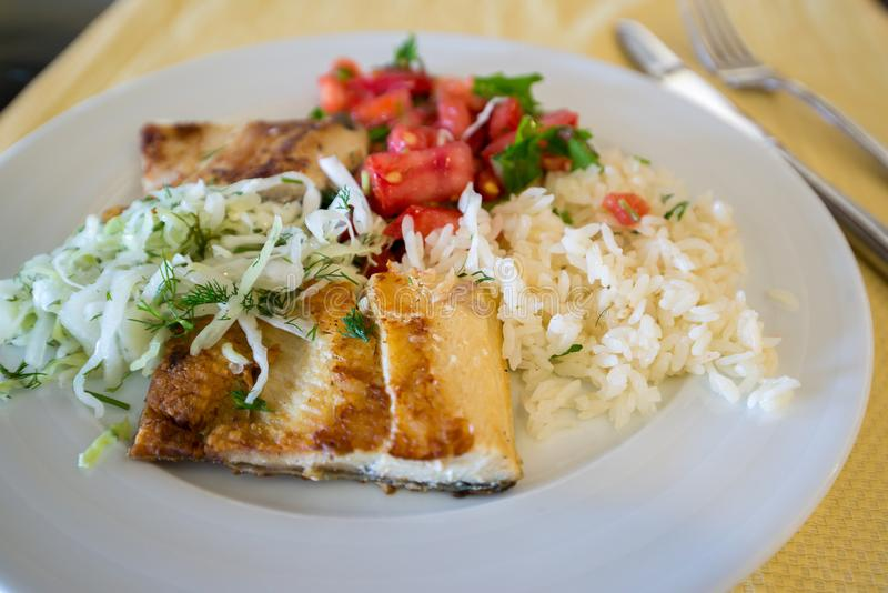 fried fish with rice cabbage and tomatoes on plate stock image